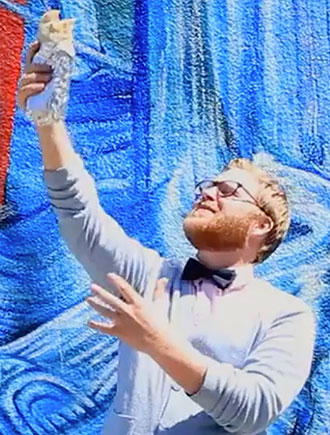 California Dream Eater, Chase Ramsey, holding burrito above head with one hand in front of a blue abstract graffiti wall.