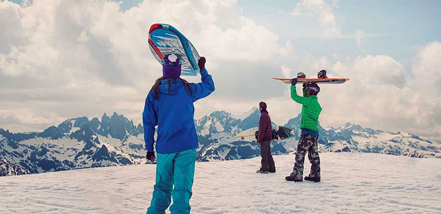 Three snowboarders holding their boards look out at snow covered mountain views.