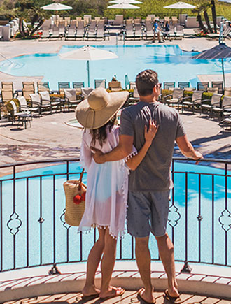 Couple at hotel resort spa, looking out over balcony at two pools and the ocean.