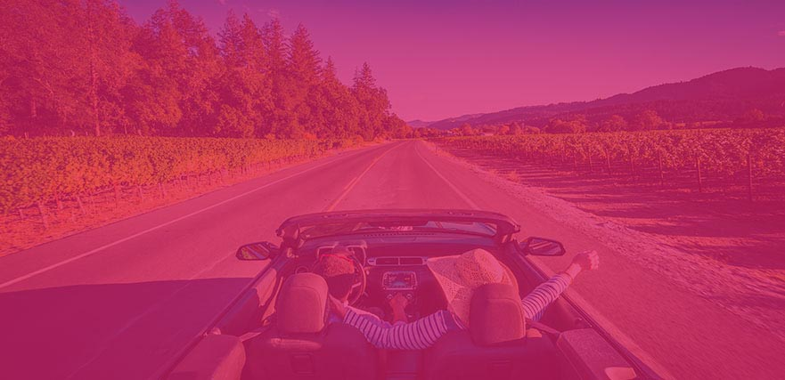 Couple in convertible car driving through vineyards with forests and mountains in the distance.